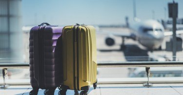 Two suitcases in the airport departure lounge, airplane in the blurred background, summer vacation concept, traveler suitcases in airport terminal waiting area, empty hall interior with large windows, focus on suitcases
