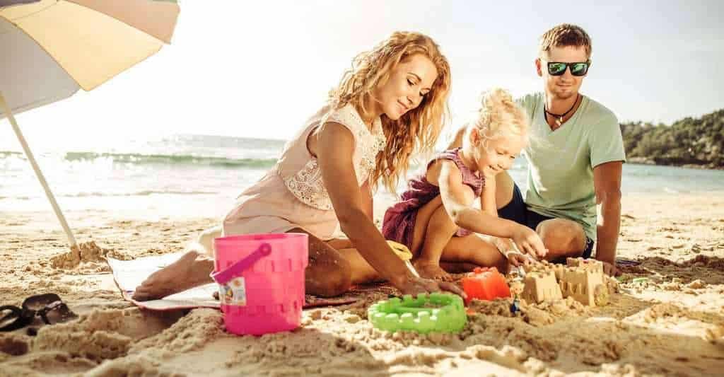 fillette construisant un château de sable avec ses parents