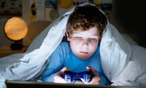 enfant dans son lit jouant aux jeux vidéo