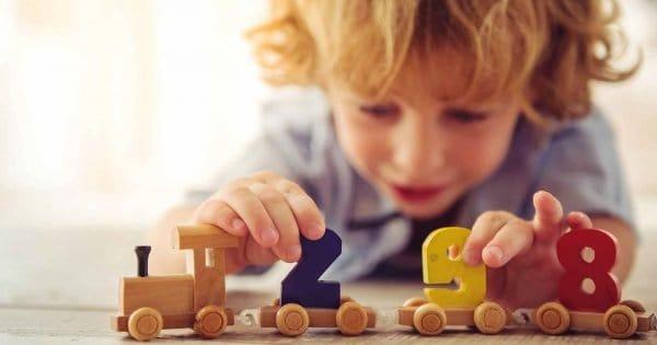 enfant jouant avec un train en bois