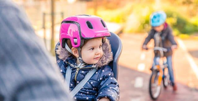 enfant en bas âge sur porte vélo