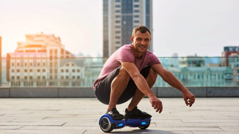 homme souriant sur son hoverboard