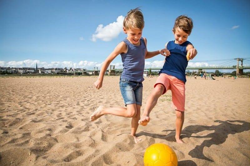 deux petits garçons au ballon sur la plage