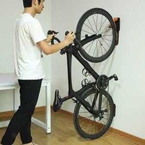 homme utilisant un porte-vélo mural